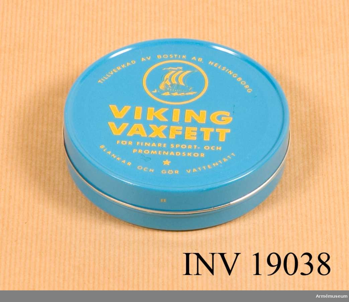 Viking vaxfett tillverkad av Bostik, Helsingborg för finare sport och promenadskor. Blankar och gör vatentätt. En blåmålad  plåtburk innehållande en ofärgad skokräm. Text i gult på över och undersidan. Burken är rund och består av botten och lock.