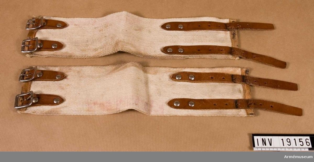 Damasker, vita 1 par 1939 ca. Användes till snödräkten. De knäpps över snödräktens byxben och pjäxskaftet. Knäpps med två bruna läderremmar med metall- spännen.  Samhörande nr är: 19145-60, rockar, byxor, mössor m m.