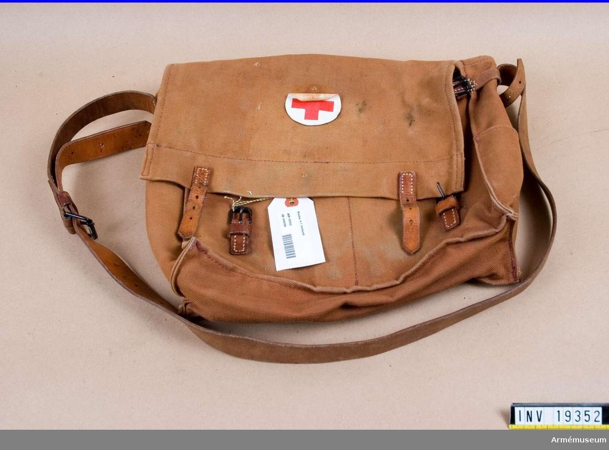 Nr 4. Bärbar väska med axelrem och spännremmar i läder och tillhörande spänne. Väskan är tillverkad av väv och läder och är märkt med  Röda Korsets märke.