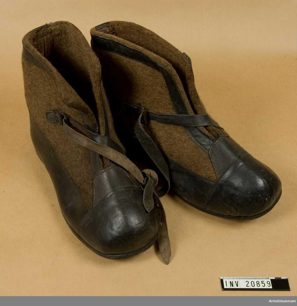 Grupp C. Ur uniform för manskap, Första världskriget 1915-16, Tyskland. Av mörkbrun filt, kantade med svart läder. På framsidan finns en rem med spännen som skorna spännes fast med. Sådana skor användes för vaktposten under vintern. De sattes ovanpå stövlarna.