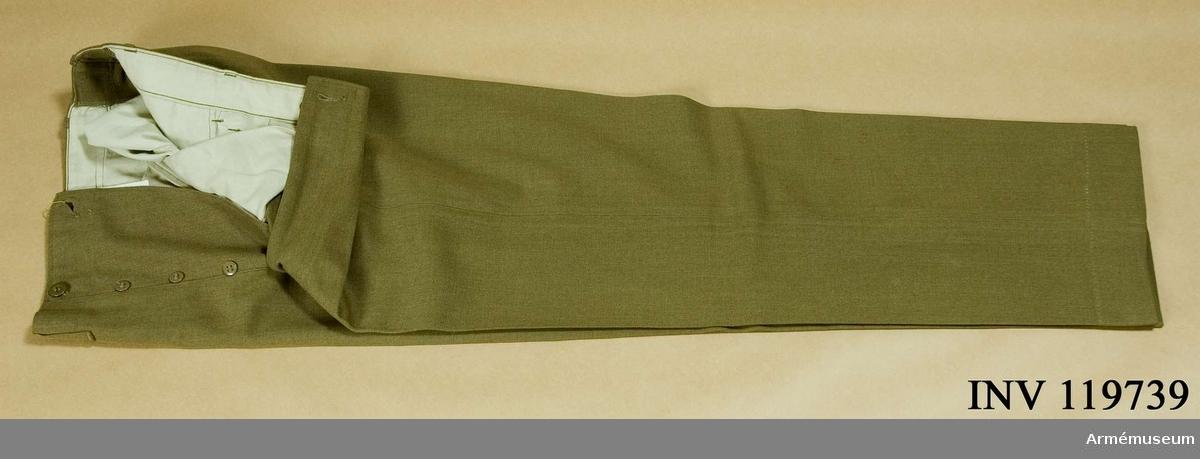 """Grupp C I. Av kakifärgat kläde. Två sidofickor, en liten ficka på framsidan vid midjan och två fickor på baksidan. På framsidan sprund med 5 knappar av ben i kakifärg. Sju löpare fastsydda vid midjan. Foder av ljust bomullstyg. På fodret stämplar: """"G - 0265"""", """"Gillespie 0265 W"""" och en liten etikett av vit bomullstyg med text """"W 31. L 35"""". På fickan finns också påskrift """"Gillespie"""", """"265 W""""."""