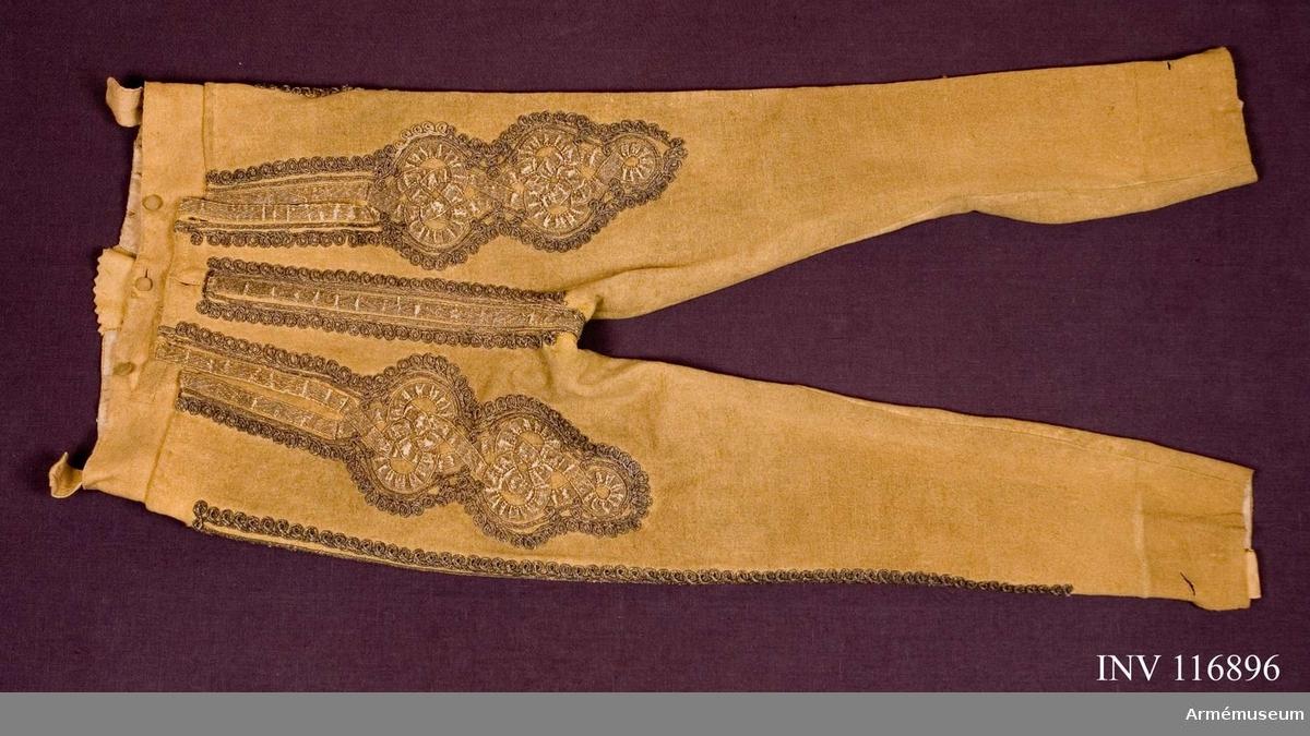 Grupp C I.  Spetsbyxor av gult kläde. Ur uniform, s.k. statuniform, för regementstrumslagare vid K. Livgrenadjärregementet. 1700-talets slut. Består av rock, mössa, byxa, plym, epåletter, svärd, balja.