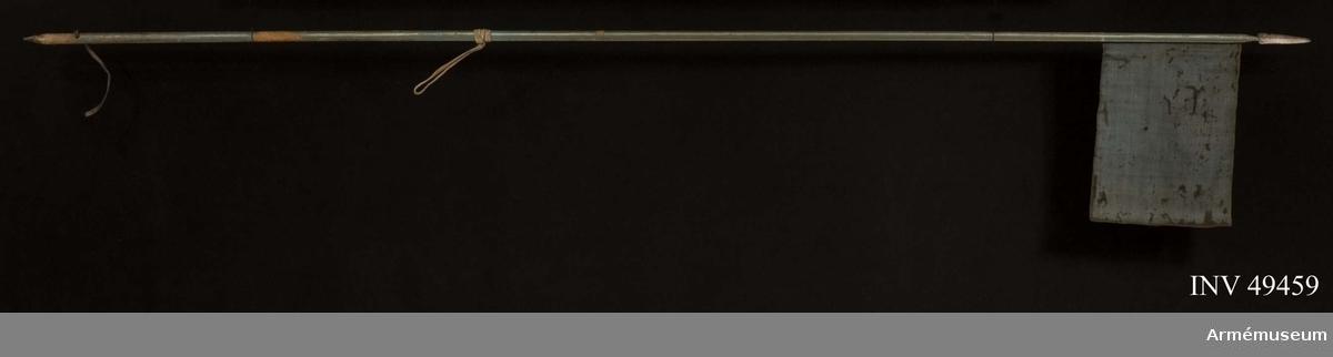 Grupp D I.  Spjutbladets längd är 150 mm, bredd nedtill 35 mm.  Holkens längd  är 40 mm. Skaftskenornas längd är 610 respektive 635 mm, deras  bredd är omkring 9 mm.  Doppskons längd är 71 mm. Spjutbladet är tveeggat med ryggar. Holken är kort och konisk.  Skaftskenorna är ej fästa vid holken. Udden är skadad.Skaftet är av furu. Nedtill har den en konisk doppsko av järn.  Upptill är skaftet på vardera flatsidan förstärkt med en smal påspikad skaftskena. Skaftskenorna är upptill instuckna i  holken. Skaftet, skaftskenorna och spetsholken är målade ljusblå  med fyra längsgående, ca 7 mm, breda vita ränder.  Ungefär 160 mm ovanför lansens nedre ände genombryts skaftet av ett hål, genom vilket går en rem, som ursprunglien bildat en sluten ögla.  Skaftet är en bit ovanför detta hål avnött.Den fastspikade flaggan är 570 mm lång och 390 mm bred.  Den är  ljusblå och rektangelformad, baktill är den förstäkt genom ett  pålagt band.