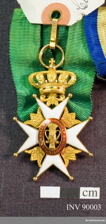 """Grupp M II. Ett johanniterkors av guldkantad vit emalj: Åtta uddar som var och en slutar i en kula. Mellan korsarmarna öppna kronor av guld. Ovanpå korset en oval med en sädeskärve inom en röd ram med text i guld: """"GUSTAF III INSTIKTARE MDCCLXXII"""", lika på åtsida som frånsida. Korset hänger i en kunglig krona.  Medaljband av grön rips."""