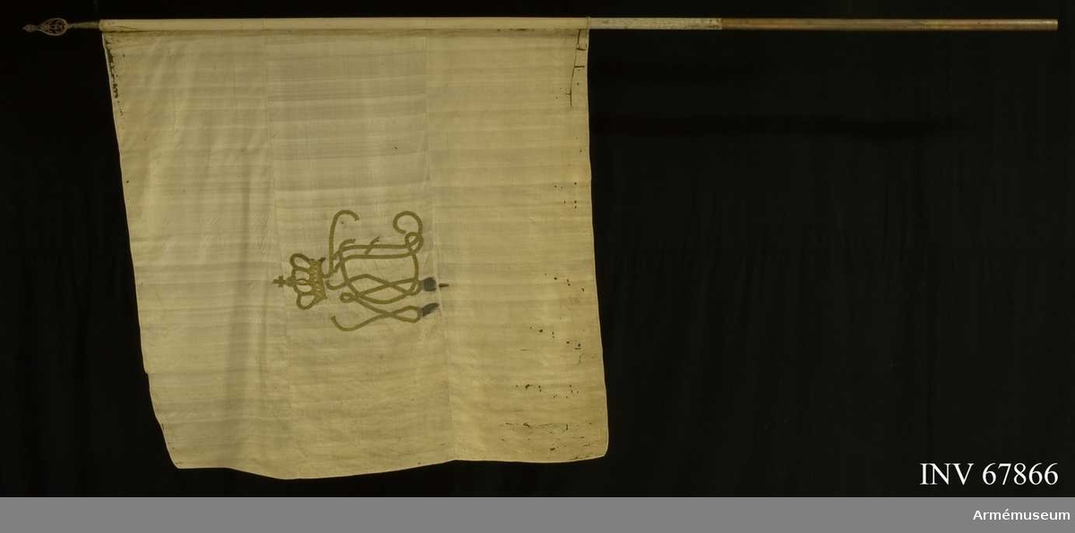 """Duk: Tillverkad av vit sidenkypert. Sydd av tre horisontella våder. Dekor med påsydda guldgaloner, omvänt lika på båda sidor: Fredrika, Dorotea Wilhelminas namnchiffer """"FDW"""" under sluten, kunglig krona (h.c. 48 cm).  Stång av furu, vitmålad.  Mässingsskaft. Spets med Gustaf III:s namnchiffer. (ej nämnt hos Cederström)."""