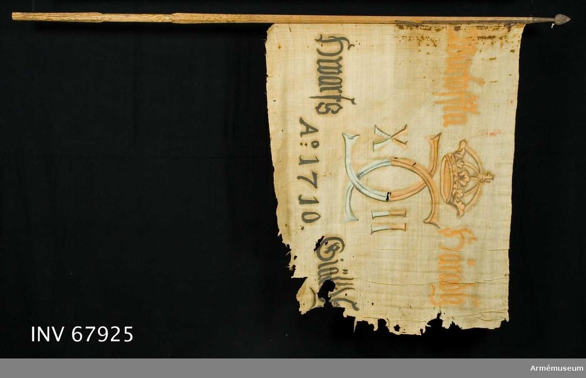 Duk: Tillverkad av enkel vit linnelärft, sydd av två horisontella våder.  Dekor:   Målad endast från dukens insida Karl XII:s namnchiffer, dubbelt C med X-II på ömse sidor, krönt med sluten krona, på det övre fältet i gult och brunt på det nedre i blått och svart. På ömse sidor om chiffret upptill i gult och nedtill i svart.  Fäst vid stången med svarta järnspikar på en läderremsa.   Stång av trä. Holk och spets lansettformade.