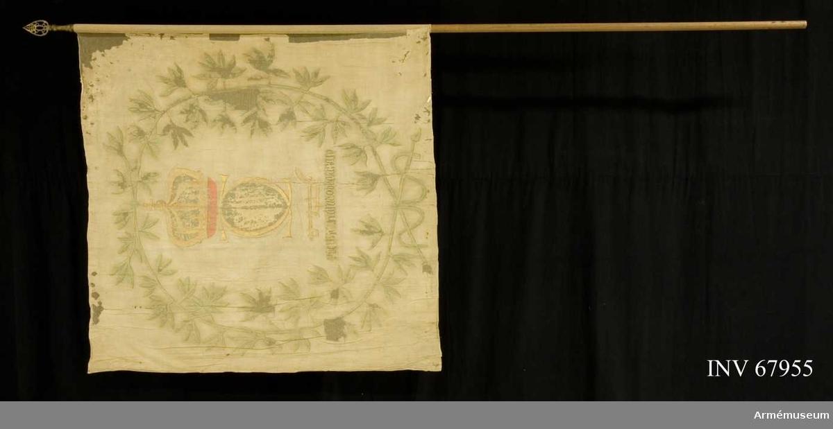 Duk: Tillverkad av enkel vit linnelärft. Sydd av en våd.   Dekor: Målad lika på båda sidor, i gult med vita och bruna skuggor, Karl XII:s namnchiffer, dubbelt C därinom XII på blå botten, krönt med sluten krona med rött inner- och blått ytterfoder. Under chiffret en plog. Under plogen en text i svart på grå botten.  Allt omslutet av en stor krans bildad av två lika lagerkranskvistar, nedtill hopknutna med vitt och brunt band. Fäst vid stången med kreppelin.  Stång: Tillverkad av trä. Spets med Carl XII:s namnchiffer dubbla C krönt med sluten krona.