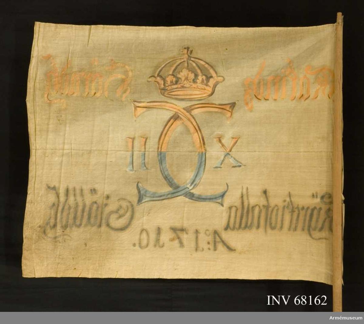 Duk: Tillverkad av enkel vit linnelärft, sammankastad av två våder (horisontell söm). Dukens vertikala fåll lagd åt utsidan. Fäst med en rad mässingsstift.  Dekor: Målad endast på dukens insida (kronan och namnchiffret ifyllt på utsidan) i mitten Carl XII:s namnchiffer med sluten krona krönt, dubbelt C, på ömse sidor om detta X-II i gult och brunt på övre våden, i blått och svart på den nedre. Text på ömse sidor om chiffret, upptill i gult och nedtill i svart. Under chiffret text i svart.  Stång: Tillverkad av trä, avsågad. Avsmalnande upptill och nedtill (avfasad).