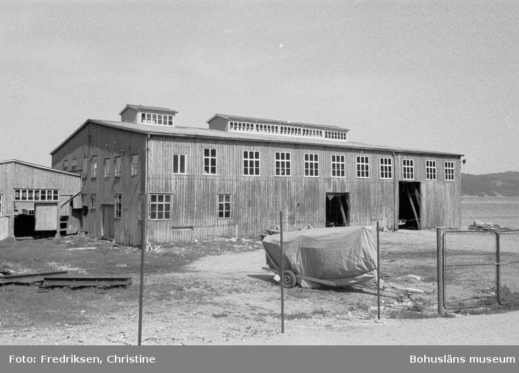 """Motivbeskrivning: """"Båtbyggarmagasin, till vänster byggnad som tidigare inrymde bl.a. matsal och utrymme för cirkelsåg""""."""