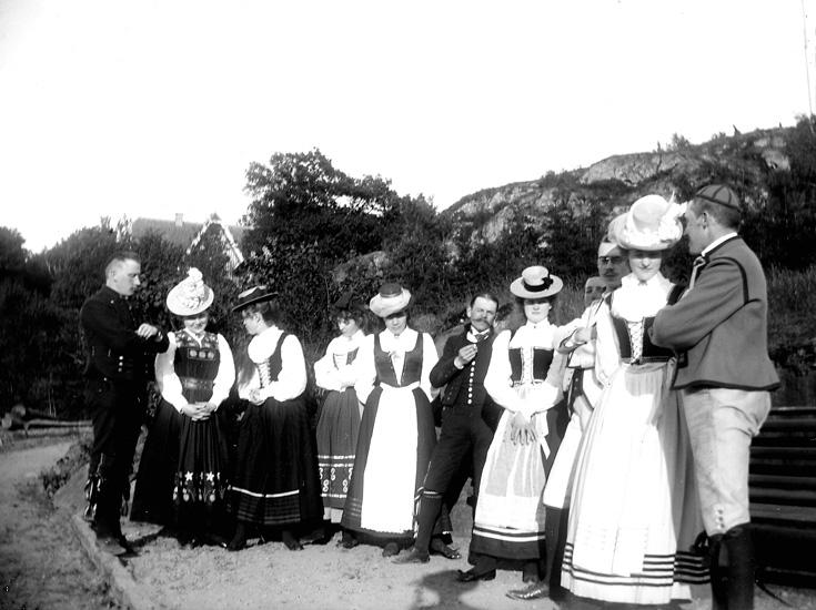 """Enligt fotografens noteringar: """"Grupp nära bryggan."""" Plats: Lyckorna Datum: 10 Juni 1899 Tid: Kl 7 e.m. Ljus: Solsken Bländare: No 2 Objektiv: Svenska Express Exponering: Hastighet No. 3 Framkallning: Hydrochinon, Eikonogén"""
