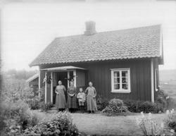 Tre kvinnor och en pojke i sjömanskostym, står framför veran