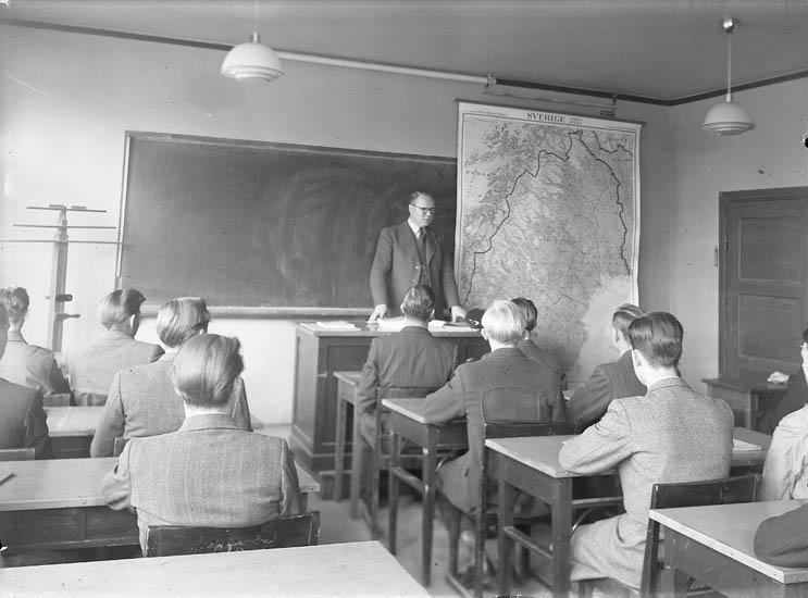 """Text till bilden:""""Lärere med några elever. Lärarens namn Asketun""""."""