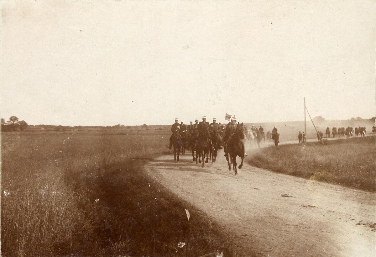 Kavalleritrupp galopperar fram på grusväg. Civila åskådare tittar på vid sidan om.