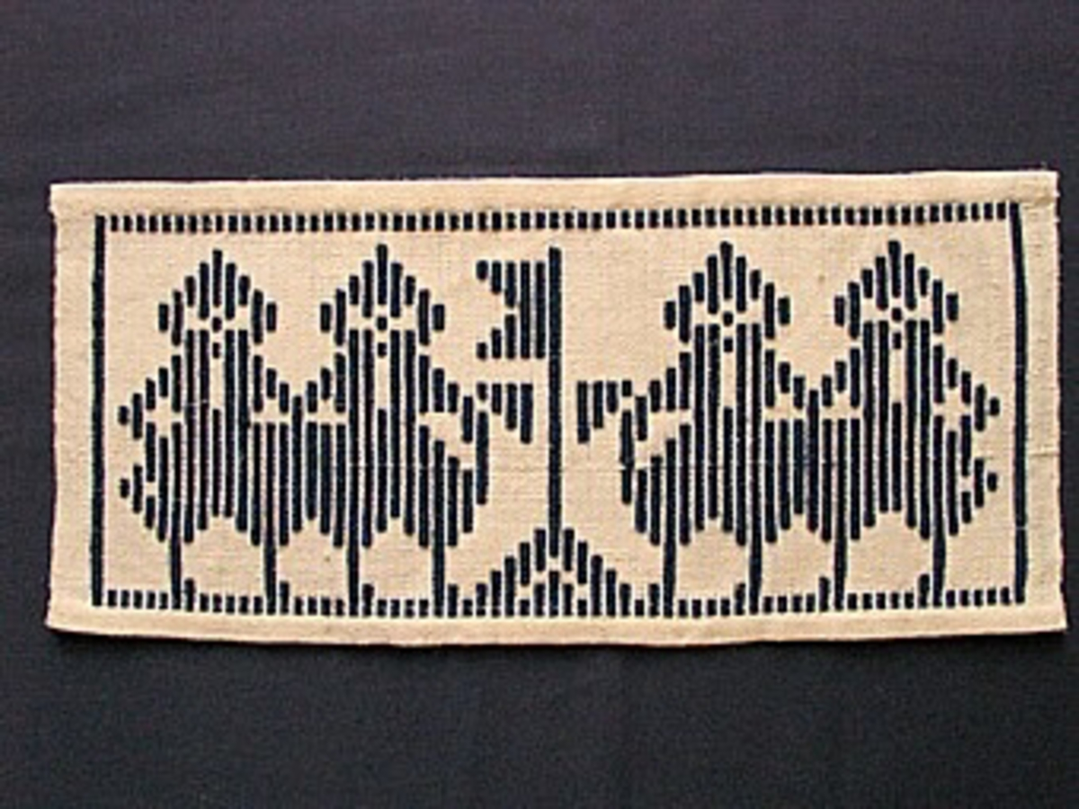 Liten rektangulär dukagångsvävnad. Botten i halvblekt lingarn, mönstret i tvinnat marinblått ullgarn. Motiv: fyra män, två på var sida om en flagga, med pösiga kortbyxor och toppiga mössor. Smal vävd ram runt om.