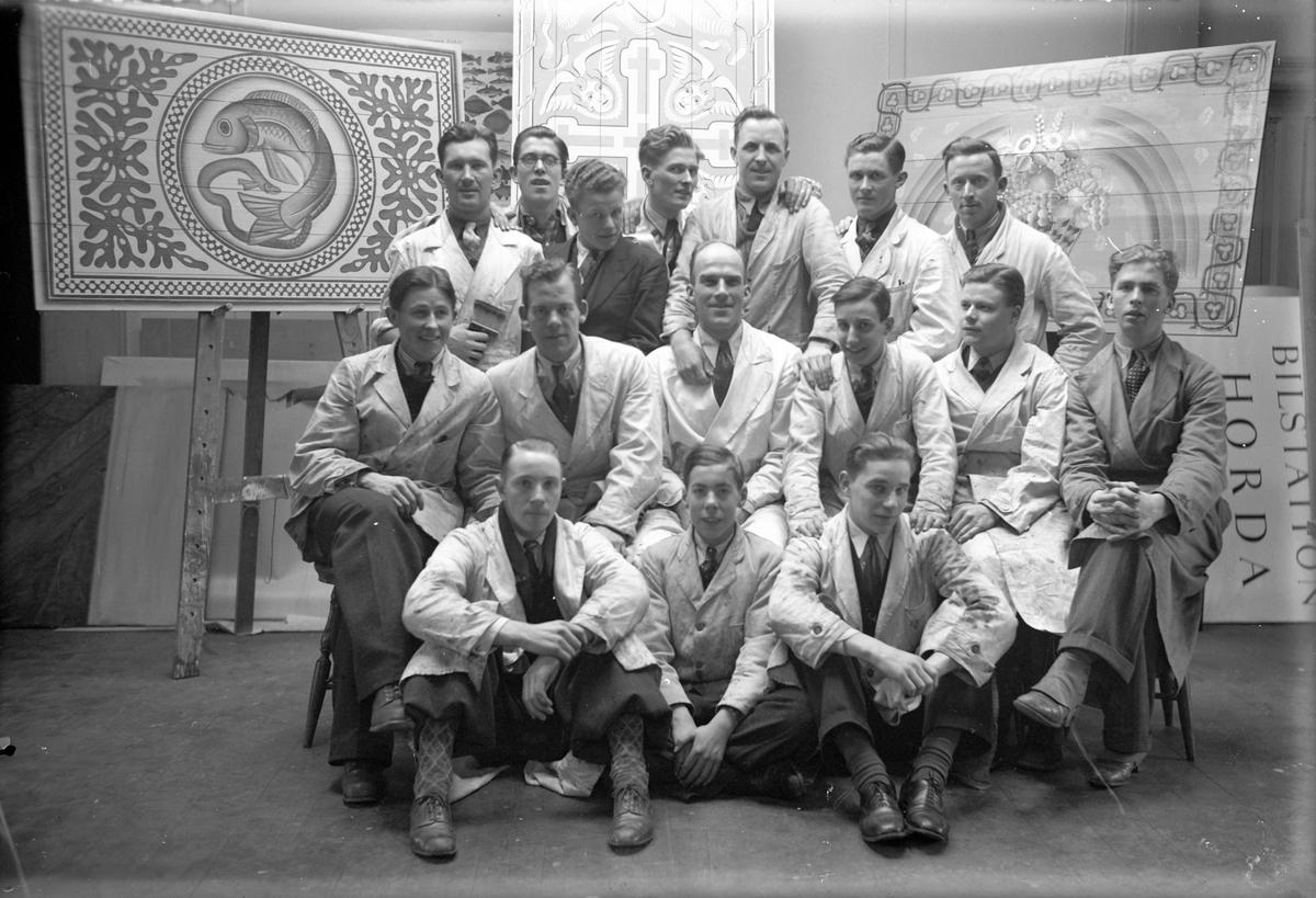 En grupp yrkesmän med sakrala motiv på tavlor i bakgrunden.