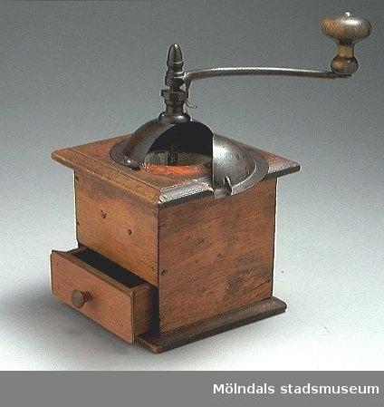 Kaffekvarn med vev och trähandtag. Från runt 1910.Tillverkarens metallmärke saknas. Lådan tillverkad senare - sprucken. Porslintratten sprucken på flera ställen.Kaffekvarnen användes för att mala kaffebönor till pulver.