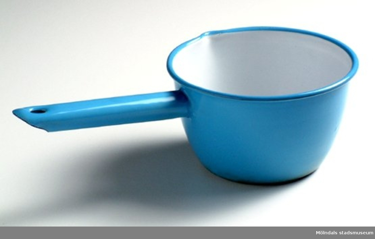 """Liten såskastrull, blå utvändigt och vit invändigt, från cirka 1920.  Snås. Skaft med hål för upphängning. Saknar utvändig fals. Märkt på undersidan: """"Kockums Sweden 12 cm""""."""