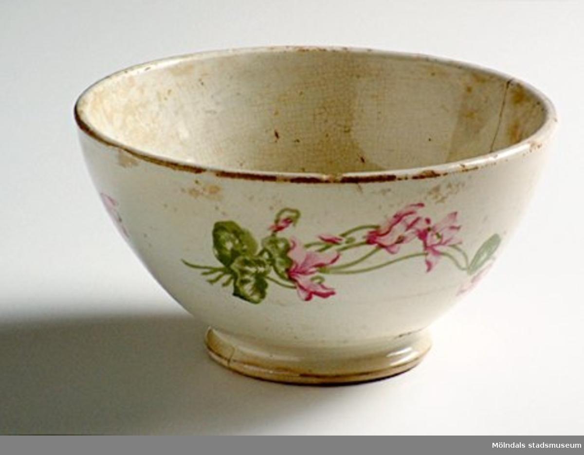 Rund skål på fot med vit glasyr. Naturalistiska blomrankor längs utsidan i grönt och rött. Materialet ev. fajans. Troligen tillverkad efter 1880.