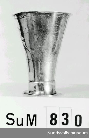 Bägare. Koniskt insvängd. Runt livet svisselerad dekor av bommor och blad. Graverad inskription: 'H.L.I. 1839 J.J.P. 1866 I.I.S.'. Stplr: A.J. Lignell, Sundsvall 1822. Jämför SuM 0832, 0834, 0850, 0852, 0882, 0911. Litteratur: Andrén, E., Svenskt silversmide 1520-1850, Nordisk Rotogravyr, Sthlm 1963, sid 525.