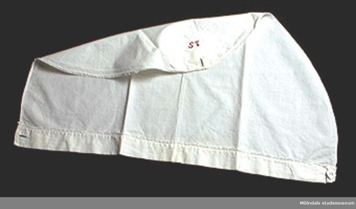"""Snibb i form av triangelformat tygstycke, som knäpps med en tygklädd mässingsknapp. Längs framkanten finns en broderad bård. Märkt med rött garn: """"ST""""."""