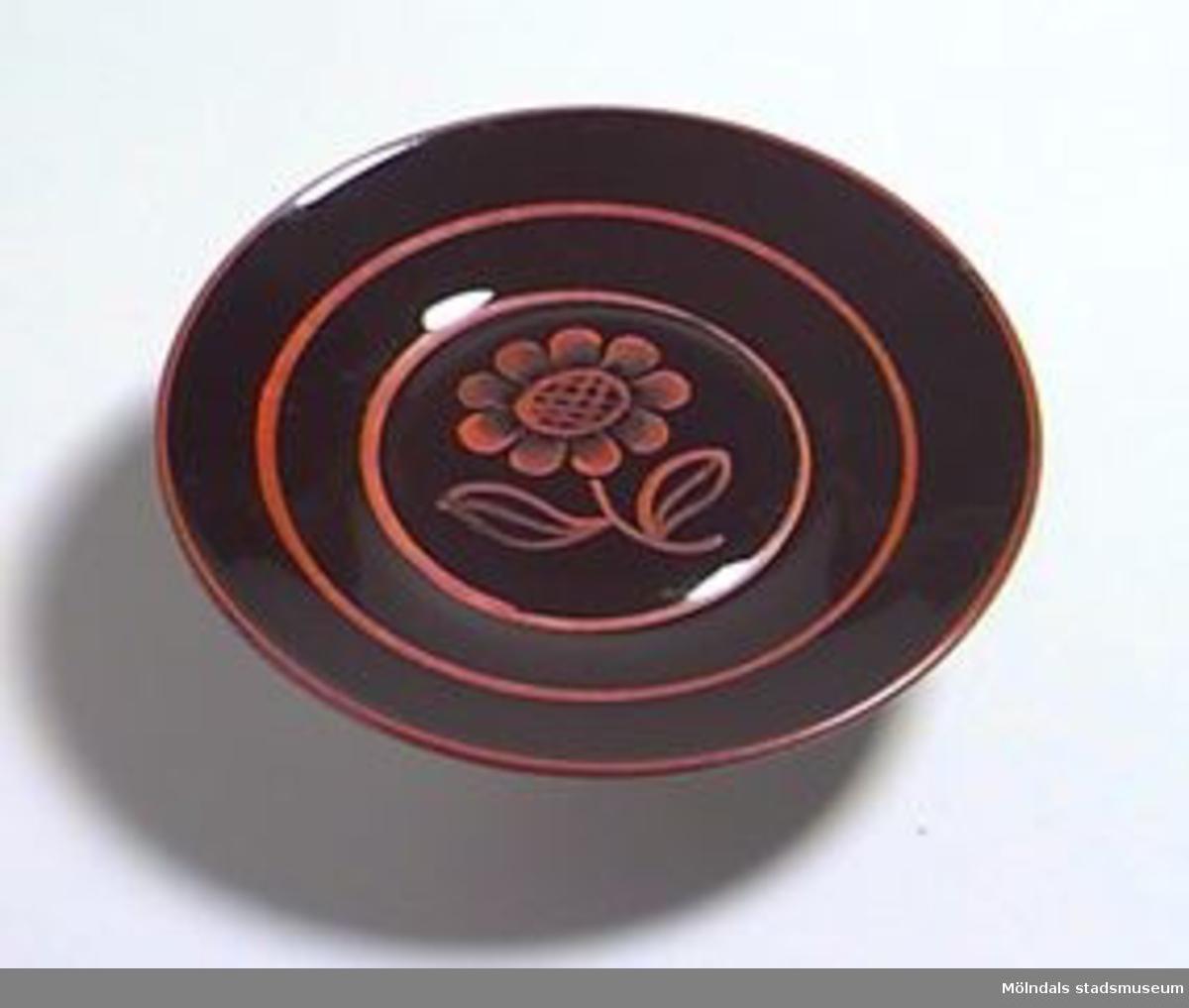 11 st svarta assietter med handmålad röd dekor i form av en blomma i mitten och ränder runt om. Dekoren delvis bortnött på några assietter.