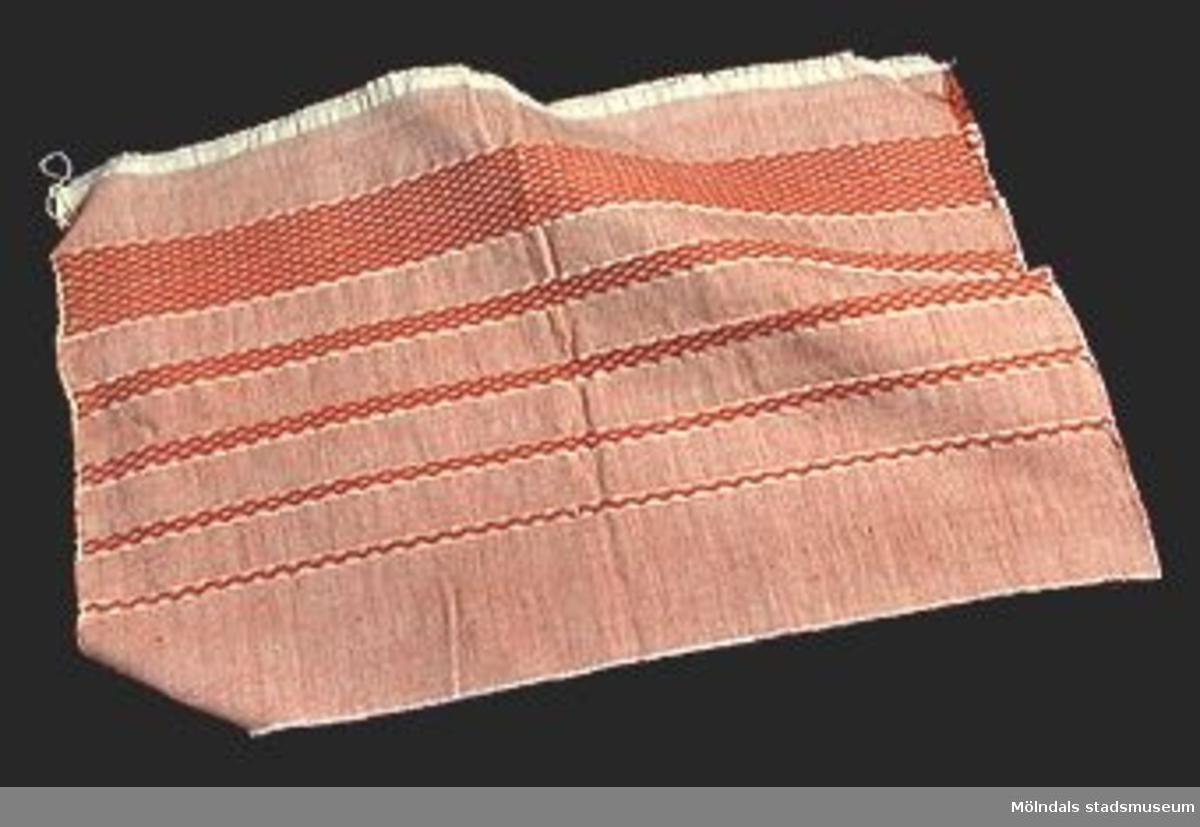 Brun tygbit med berget mönster i ränder, prov på hålkrus.Elevarbete från textillärarseminariet.Gåvan förmedlad genom Gustav Wickström.