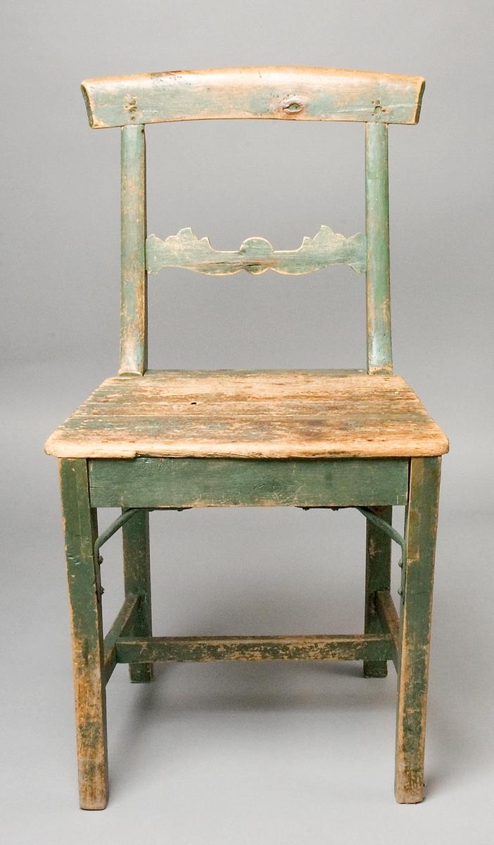 Stol, handgjord av trä, björk och furu. Modell som efterliknar Karl-Johansstilens ideal. Alla delar av björk utom sitsen. Lätt svängda framben, h-kryss med raka slåar. Bakben och sidoståndare i ett, lätt svängda. Överstycket är lätt format och avfasat, och är fäst framifrån i avfasningar i sidoståndarna. Ryggslå med dekorativt utformade sidor. Stolen är målad i grön oljefärg, nu mycket nött.