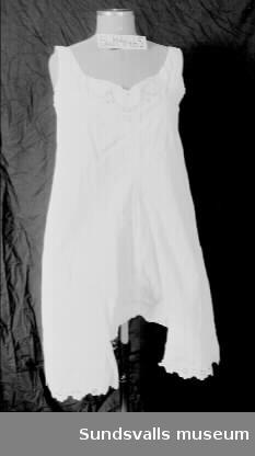 Vita kvinnounderkläder i bomull. Ärmlös. Tät langettsöm i hals, ärmhål och på brodyren längst ner på benen. Broderat monogram mitt fram. Lucköppning i ryggen som knäpps med tre tygklädda knappar.