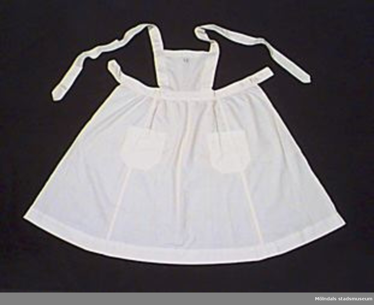 """Vitt förkläde med två fickor fram. Fram på bröstpartiet märkt med blått broderat garn i korsstygn; """"I S"""". Axelband som knäppes i livet. Livet knäppes baktill. Tillverkad tillsammans med babyutrustning."""