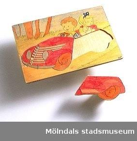 """Kontursågat i plywood, motiv """"barn i bil"""". Ingår i Holtermanska samlingen."""