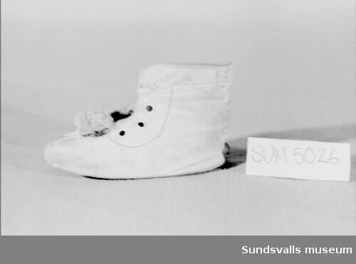Barnsko i vitt läder fodrad med rosa flanelltyg och med hålen för skosnöret förstärkt med en metallring. Skon använd av givaren, född 1930.