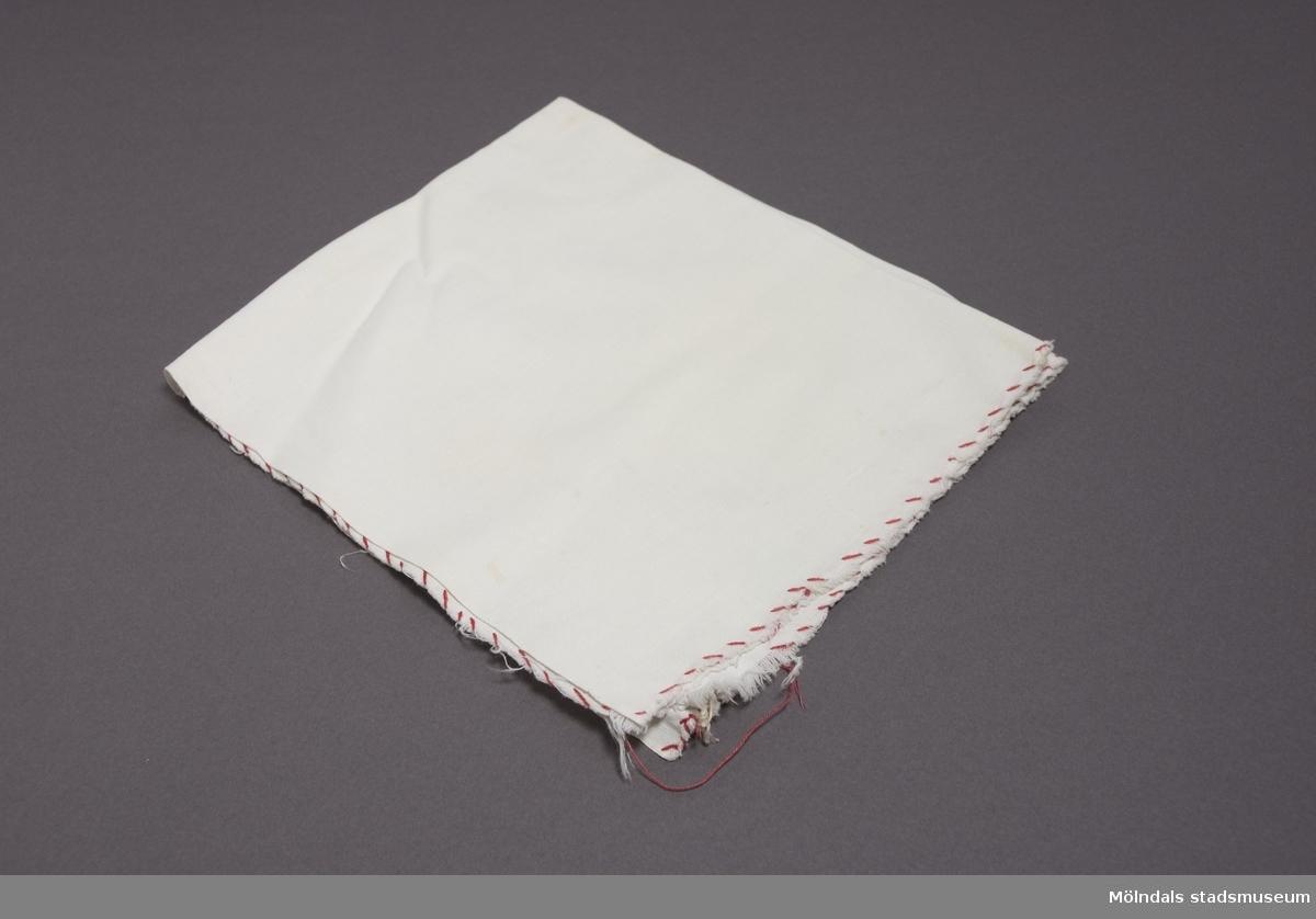 Tvättlapp i vit bomull, kastad med röd tråd.