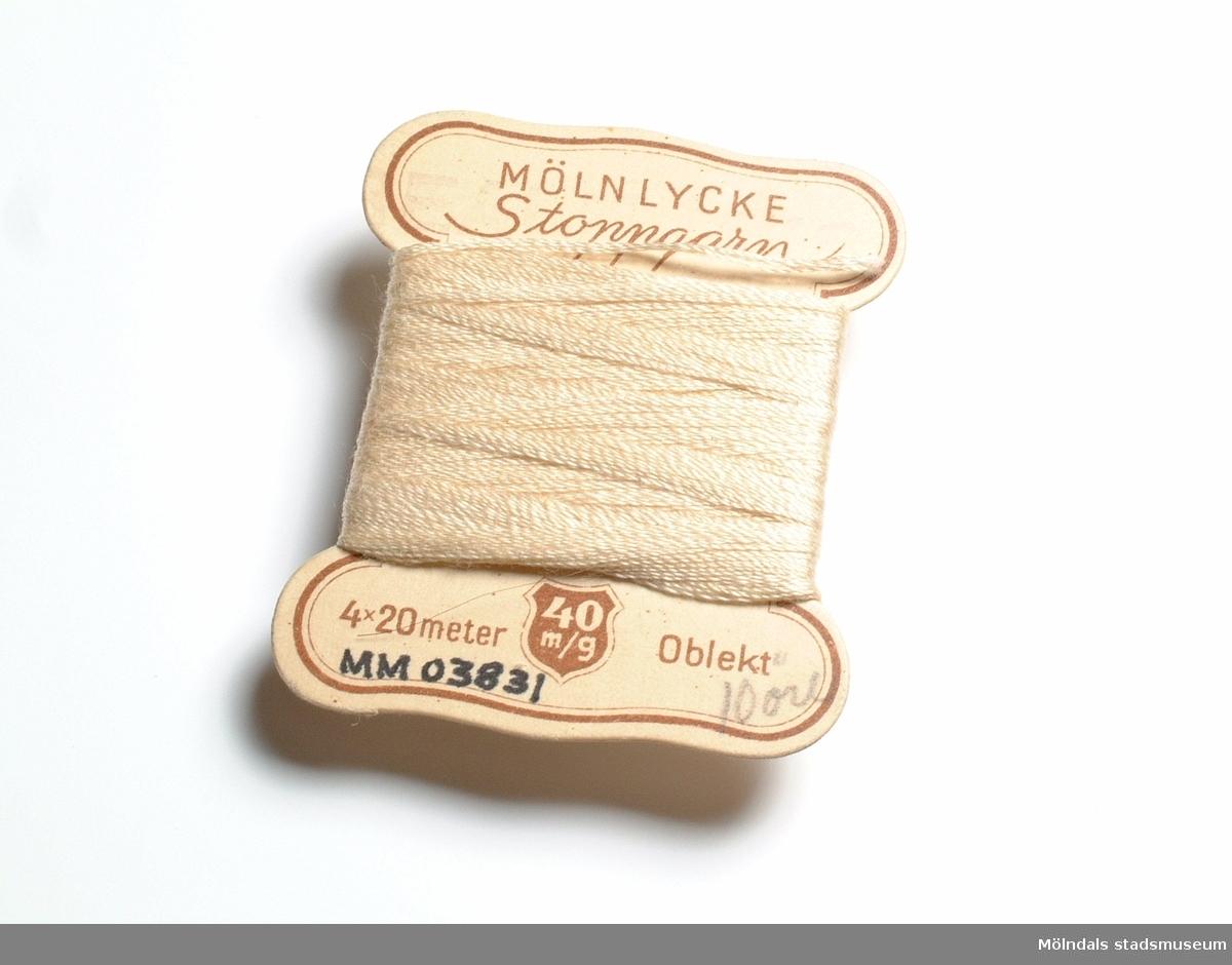 Oblekt, mercericerat bomullsgarn upplindat på en pappskiva, märkt Mölnlycke Stoppgarn, 4*20m, 40m/g. Pris 10 öre.Stoppgarnet användes för lagning av bomullsunderkläder till barn och vuxna. Det användes även för lagning av bomullsstrumpor, främst till barn.