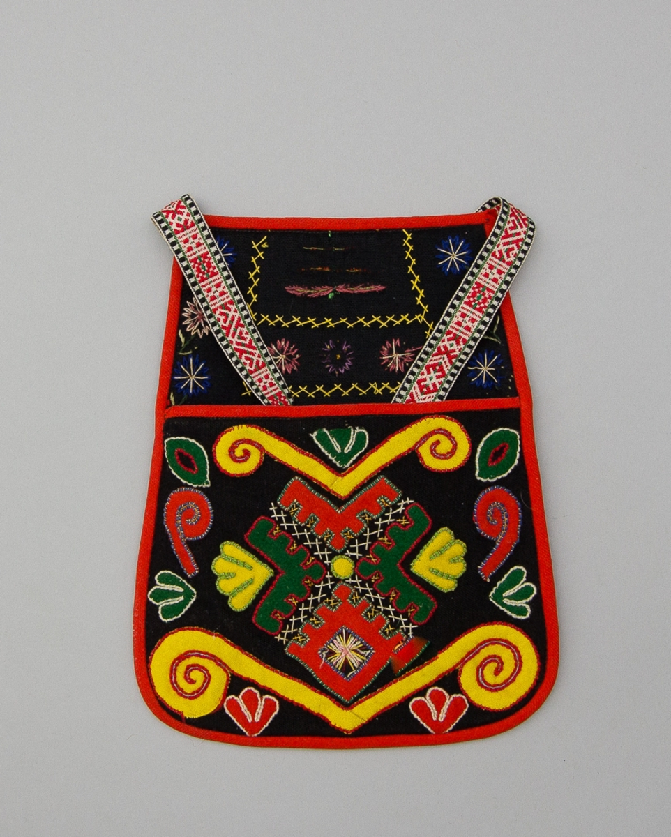Kjolsäck till dräkt för kvinna från Gagnefs socken,  Dalarna. Modell med avskuret framstycke. Tillverkad  av svart ylletyg, kläde, med applikationer i rött, gult och grönt kläde, fastsydda med ullgarn, läggsöm. Centralt placerat motiv med trekantiga figurer, omgivna av slingor och bladformer. Sparsamt broderi utfört med bomullsgarn, flätsöm och sticksöm. Överstycket broderat med samma stygnsätt, rader och blommor. Framstycket fodrat med beige fabriksvävt bomullstyg, tuskaft. Bakstycket fodrat med grått bomullstyg, hopstickat med själva bakstyckets svarta tyg. Kantad med remsor av rött kläde. Midjeband handvävt, med plockat mönster av rött ullgarn på vit botten av lin.