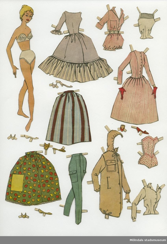 """Klippdocka med kläder och skor, urklippta ur tidning på 1950-talet. Docka samt större kläder, märkta på baksidan: """"Fia"""" - dockans namn. Dockan föreställer en ung kvinna, tecknad, med blont uppsatt hår, iklädd vita underkläder. Garderoben består av en jacka med kapuschong, två klänningar, en dress med korta ärmar och ben, en axelbandslös baddräkt, vit skjorta, vit ärmlös top, två kjolar, ett par byxor, samt fem par skor. Docka och kläder förvaras i ett brunt kuvert, 12,5x15,5 cm. Tryckt avsändare är Göteborgs Arbetarekommun. Kuvertet är frankerat och poststämplat den 3 juni 1957, märkt """"Fia"""" på framsidan med utklippta, fasttejpade bokstäver."""