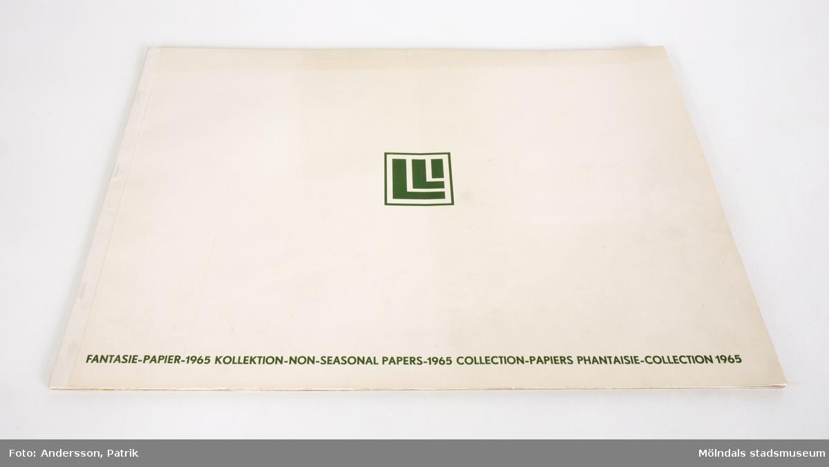 """1st bok/häfte med flera pappersprover med olika mönster och motiv.Dassa pappersprover kan ha varit prover för Presentpapper, Kökslådepapper eller Bordsdukar.Varje pappersark har ett motiv eller mönster. På baksidan av varje ark står det ett nummer och vad det är för möster.Omslaget av pappersprovboken är vitt. På framsidan längst ner står det tryckt med mörkgröna bokstäver: """"FANTASIE-PAPIER-1965 KOLLEKTION-NON-SEASONAL PAPERS-1965 COLLECTION-PAPIERS PHANTASIE-COLLECTION 1965""""Det finns också en mörkgrön logga i mitten av framsidan.Storlek på pappersprovsboken:Längd: 335 mmBredd: 486 mmDjup: 4 mm"""