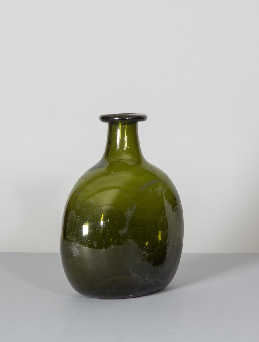 Flaska i grönt glas. Tillplattad modell med rundade sidor. Hals med bred halsring. Likheter med den tyska Bocksbeutel.