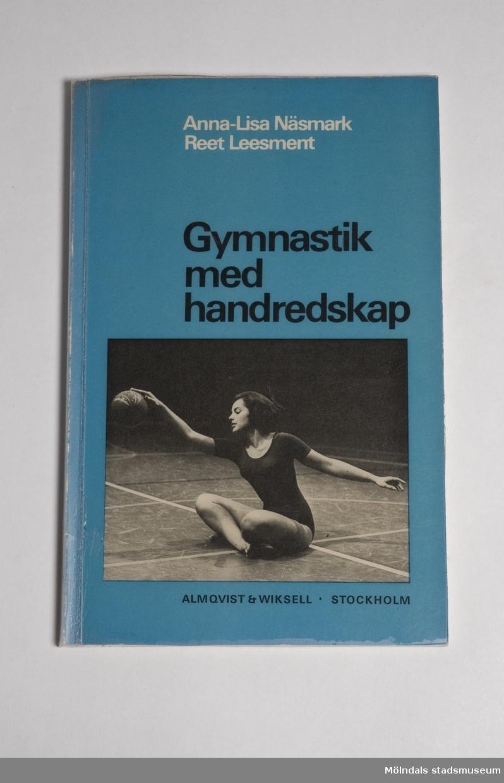 Lärobok - Gymnastik med handredskap.Boken har grön-blåaktiga pärmar som är inplastade. Det finns ett svartvitt foto på framsidan som föreställer en gymnast med en boll.