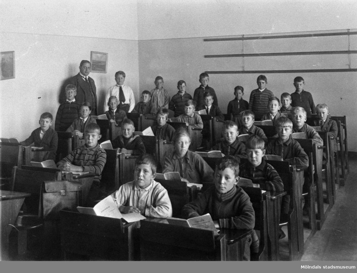 Pojkar sittande i bänkar med räkneböcker framför sig på Kvarnbyskolan i Mölndal år 1952.