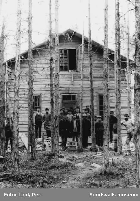 """Alby 1898. """"Baracken"""" med arbetare. Vid dörren Per From, som var snickare och arbetade i Alby. På fönstret i övervåningen ser det ut som Per Lind framkallar sina fotografier mot glasrutorna."""