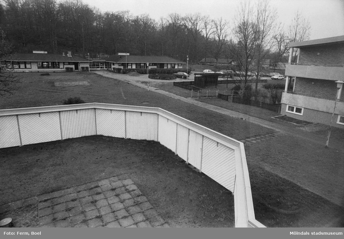 Dokumentation av Sagåsens flyktingförläggning 1992. Utsikt från en inhägnad utomhus-lekplats mot fastigheter i bakgrunden.