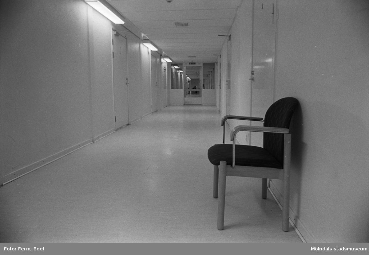 Dokumentation av Sagåsens flyktingförläggning 1992. En inomhuskorridor, med stängda dörrar på båda sidorna. Utefter väggen på höger sida står en stol. I bakgrunden ser man en stängd glasdörr.