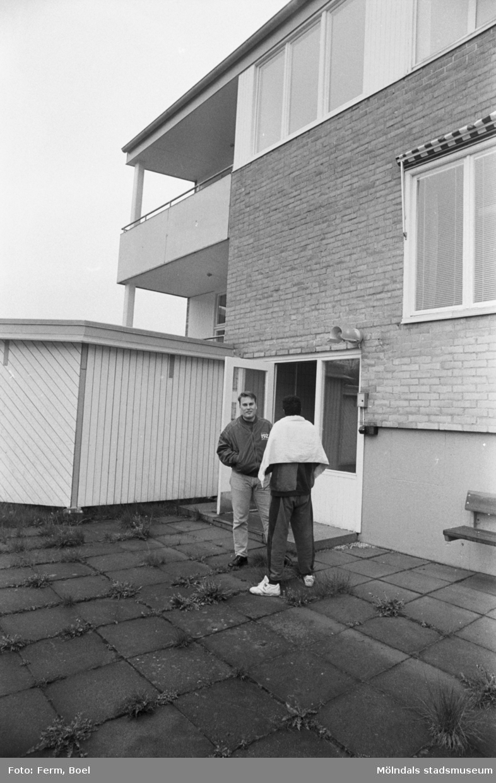 Dokumentation av Sagåsens flyktingförläggning 1992. Två personer står utanför en öppen entrédörr in till en byggnad. I bakgrunden syns ett insynsskydd.