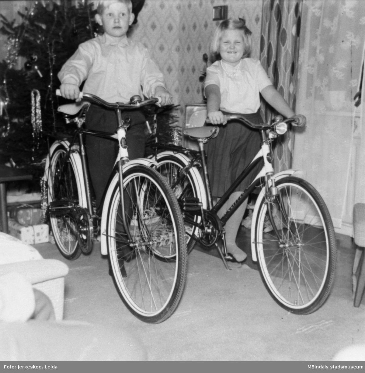 Ulf och Marita Jerkeskog poserar med sina nya cyklar, julen 1960. En julgran skymtar i bakgrunden.