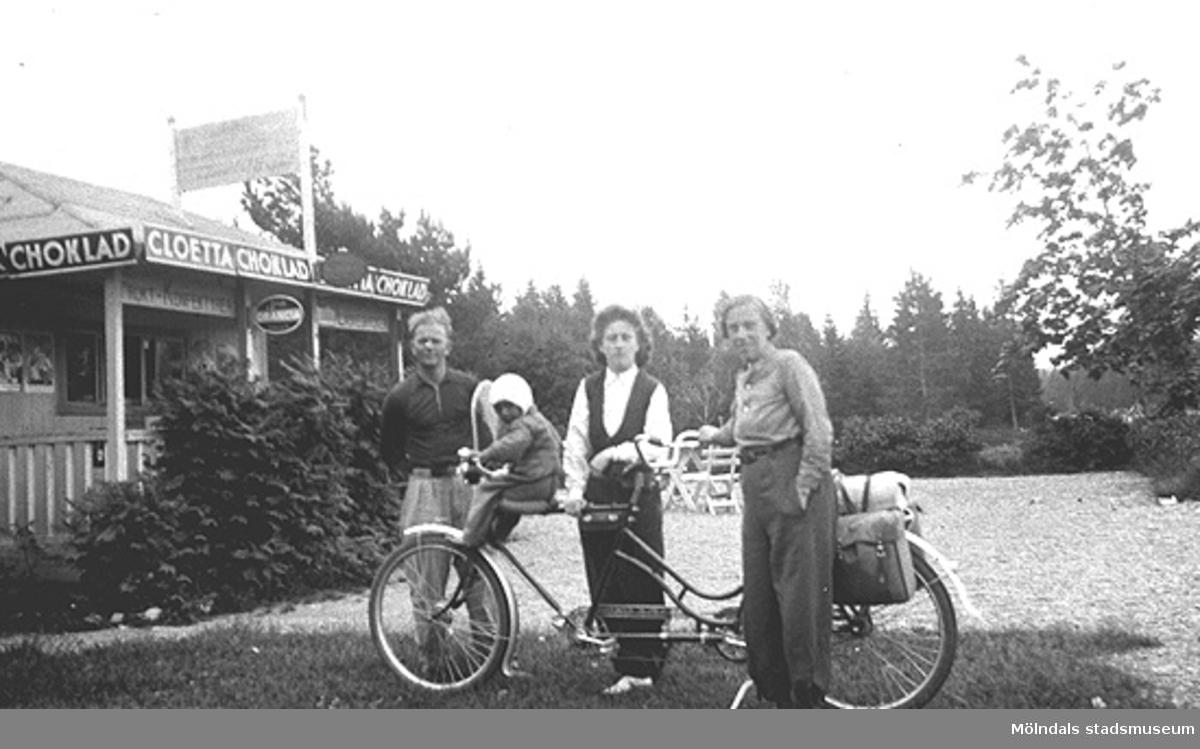 Cykelsemester på tandem i Bohuslän för syskonen Rolf (i korgen) och Astrid Karlsson (gift Garthman) samt deras mor Alma. Längst till vänster står Astrids dåvarande fästman. Astrid är givarens mor och Alma Karlsson är mormor. 1930-tal.