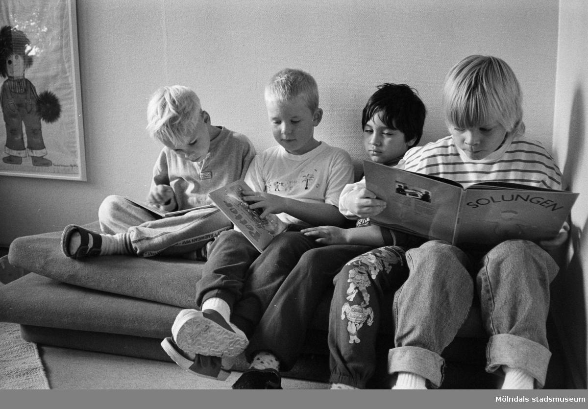 Jimmie, Pontus, Erik och Robin sitter tillsammans i en säng och läser böcker. På väggen vid sidan om sängen, hänger en tavla med ett tecknat troll. Hoppetossan, Katrinebergs daghem 1992.