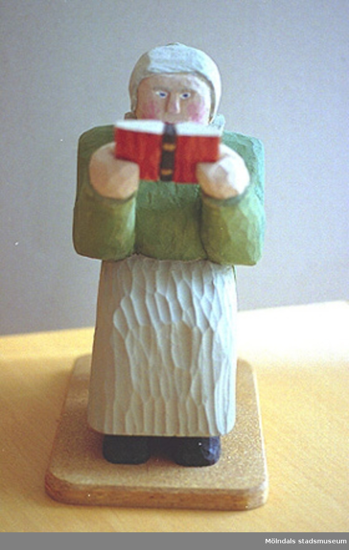 """En gråhårig gumma sitter ner och läser i en bibel. Harry Bergmans """"gubbar"""" (träfigurer)."""