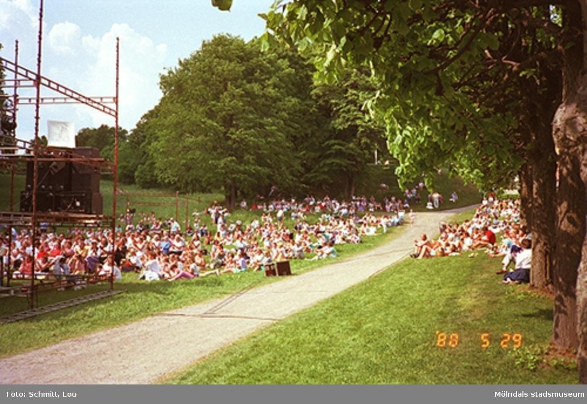 Människor sitter på gräset och lyssnar till Lasse Berghagen, som står på en tillfälligt uppbygd scen på Gunnebo slotts baksida.
