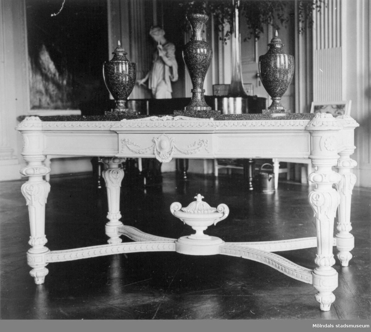 "Ett ljust, snidat bord med tre urnor stående ovanpå. I bakgrunden ser man statyn ""Våren"" (i nordost) av Gioacchino Frulli (1766-1801). Stora salen på Gunnebo slott."