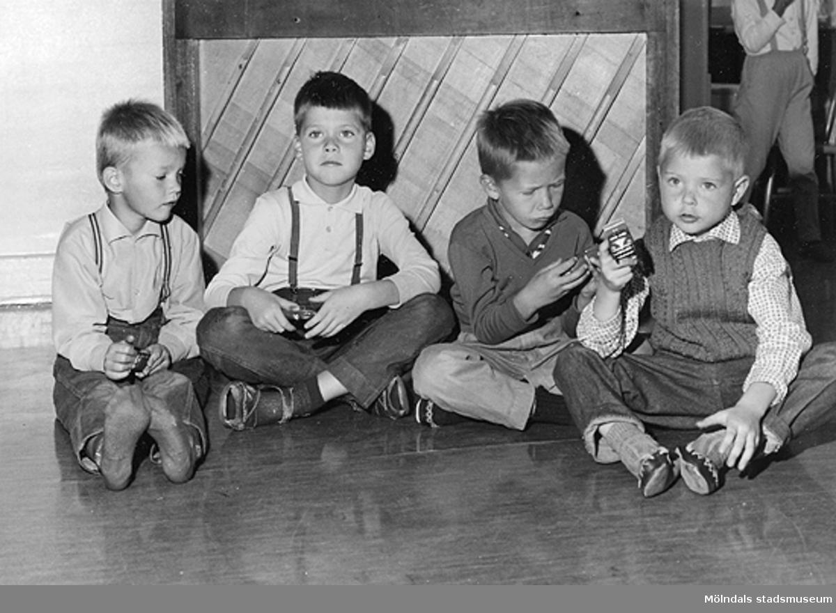 Fyra pojkar som sitter på golvet vid Holtermanska daghemmet 1953.